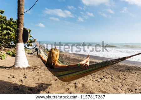 A blonde tourist enjoys the sun and sea in a hammock on the Caribbean coast of Colombia #1157617267