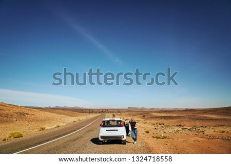 A blonde tourist girl at the car in the dessert during midday with no traffic at the road