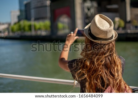 A blonde tourist makes a photo with her mobile phone next to a r Stock fotó ©