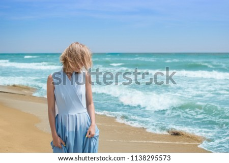 A blonde woman in a blue dress on the seashore, ocean. The concept of summer vacation, travel, vacation. #1138295573