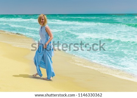 A blonde woman in a blue dress on the seashore, ocean. The concept of summer vacation, travel, vacation. #1146330362