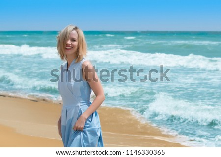 A blonde woman in a blue dress on the seashore, ocean. The concept of summer vacation, travel, vacation. #1146330365