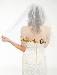 A blonde woman in a white lace dress and a white mesh bride veil turned back. The lady is showing golden writing