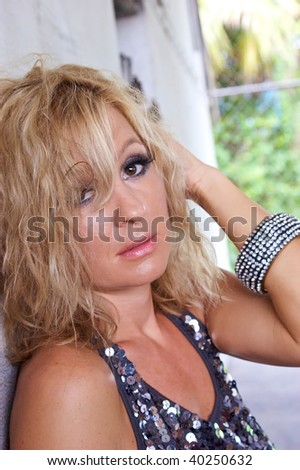 A blonde woman with big brown eyes is looking at viewer and seems very tired.