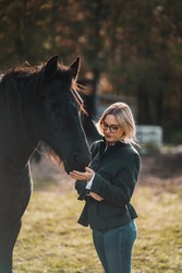 A blonde woman with glasses feeding her Frisian horse