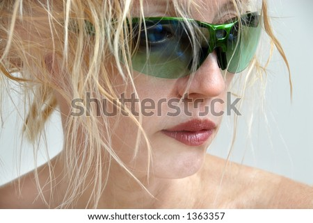 A blonde woman with messy hair, wearing no makeup other than lipstick, hiding behind green sunglasses and looking to the side.  Bad hair day.