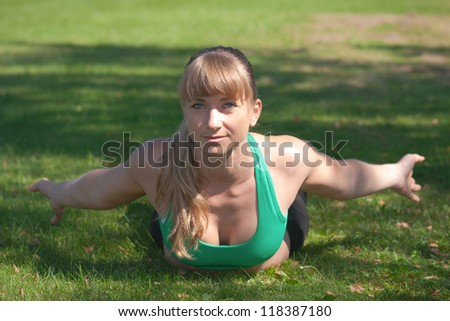 A blonde women lay in the grass . make a fitness workout