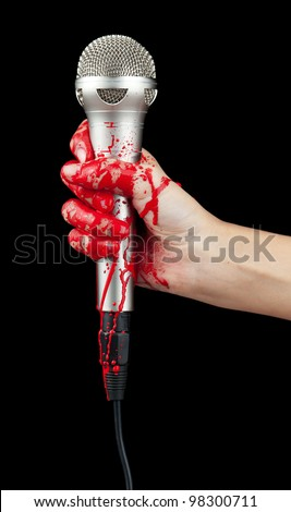 A blood covered hand holding up a silver microphone isolated on black.