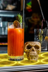 A Bloody Mary alcoholic drink on the pub counter side by side with a human cranium skull, concept of alcohol addiction.