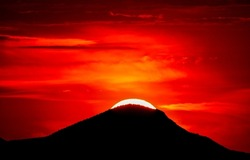 A bloody sunset behind a mountain peak. Red sunset over mountain hill. Red sunset scene. Bloody sunset