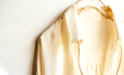 a blouse or shirt in white hanging on clothes hanger on white background.Close up and copy space.
