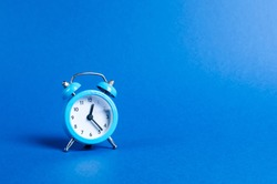 A blue alarm clock on a blue background. Limited offer and over time. Planning and discipline. waiting for a meeting. Punctuality. business planning. Life duration and health, increase your age.