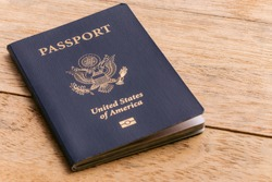 A blue American passport sitting on a wooden table