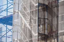 A blue and a grey net protects scaffoldings on a construction site in Berlin-City.