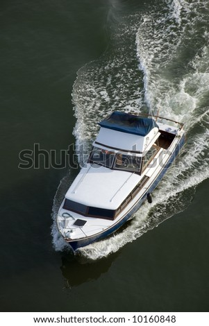 A blue and white cabin cruiser, with a wet canopy, shot from above while leaving harbour.