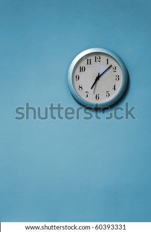 A blue and white clock on a blue wall