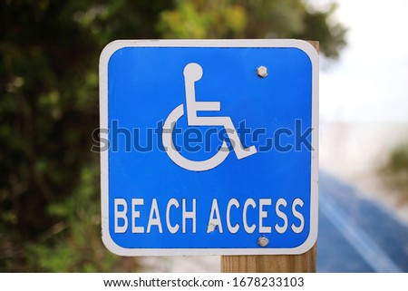 A blue and white disabled or handicap Beach access sign at a path leading to public Ocean access. Stock photo ©