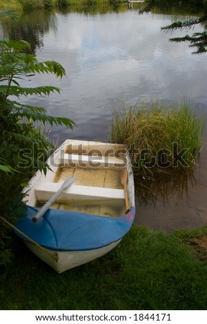 A blue and white rowboat on the shore of a pond, surrounded by nature. - stock photo
