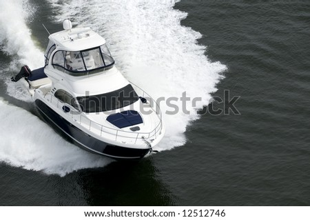 A blue and white speedboat shot from above while travelling fast.