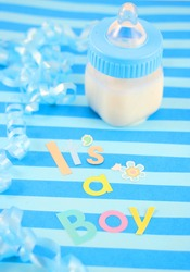 a blue baby bottle with milk and celebratory it's a boy text and  ribbon suitable for new baby