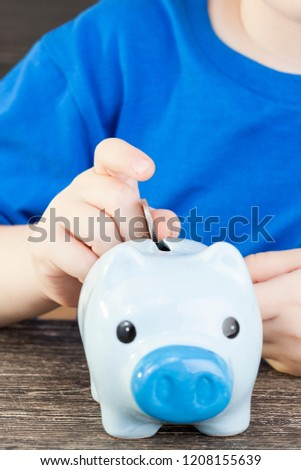 a blue bank for coins in which a child folds and saves his savings, pocket money, a pig-shaped piggy bank #1208155639