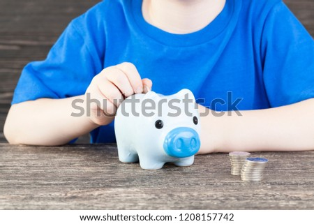 a blue bank for coins in which a child folds and saves his savings, pocket money, a pig-shaped piggy bank #1208157742