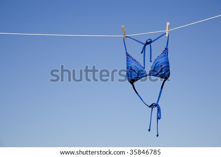 a blue bikini swimsuit top hanging on a clothesline in front of a cloudless blue sky