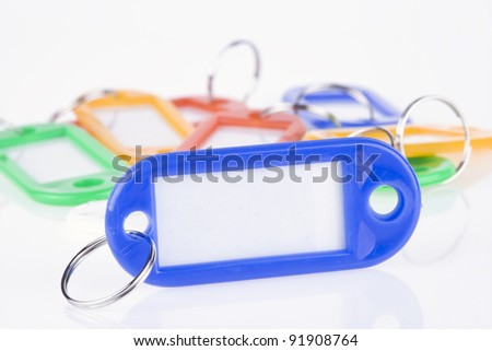 A blue blank key tag with a set of colorful blank key tags on the background