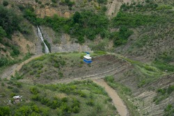 A blue cable car traveling on a ropeway over the ravine with a small waterfall. Overhead aerial shot taken in Tbilisi, Georgia. Transportation and travel.