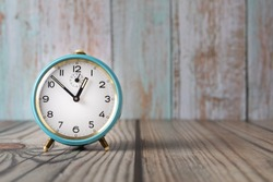 A blue classic alarm clock on a wooden background