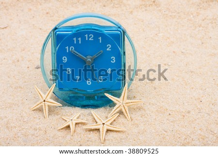 A blue clock sitting on a beach with starfish, vacation time
