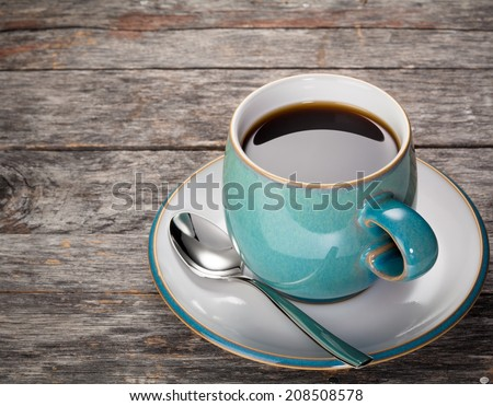 A blue coffee cup full of black coffee with a spoon on a rustic wood background.