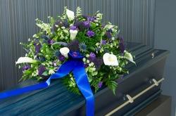 A blue coffin in a morgue with a flower arrangement