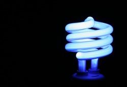 A blue compact fluorescent energy saver light bulb set against a black background.