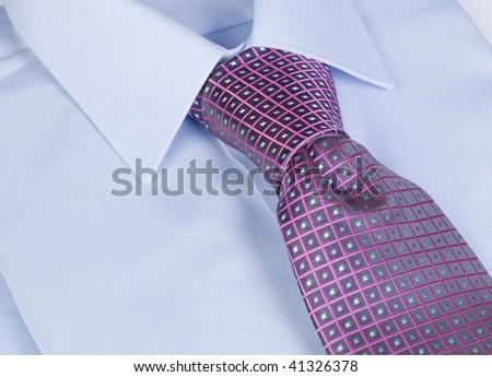 A blue cotton shirt with a purple silk tie