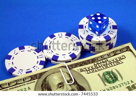 a blue die over three piles of gambling chips and bills of one hundred dollars
