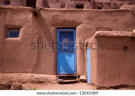 A blue door in taos pueblo adobe building stock photo for Adobe construction pueblo co