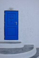 A blue door with a cross, the entrance to a small orthodox chapel in Santorini Greece
