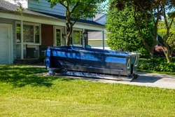 A blue dumpster in the driveway of a house in a residential neighborhood