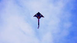 A blue flying kite. Colrful kite flying in the blue clear sky.