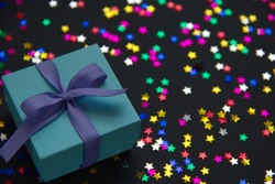 A blue gift box decorated with a purple bow and small multicolored stars lie on a black background.