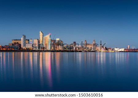 A blue hour image of the Liverpool skyline with lights reflected in the river Mersey #1503610016