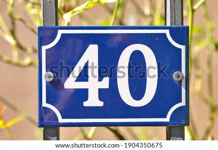 A blue house number plaque, showing the number forty (40)   Stockfoto ©