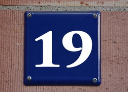 A blue house number plaque, showing the number nineteen (19)