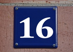 A blue house number plaque, showing the number sixteen (16)