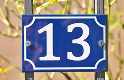 A blue house number plaque, showing the number thirteen (13)