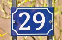 A blue house number plaque, showing the number twenty nine (29)