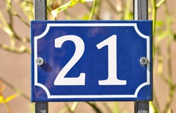A blue house number plaque, showing the number twenty one (21)