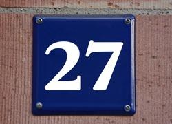 A blue house number plaque, showing the number twenty seven (27)