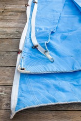 A blue jib sail rolled up on the dock with shows a close up of the bolt rope and copper hanks sewn onto the sail.